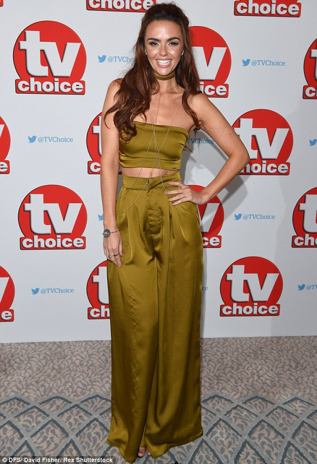 Toned:Featuring a tiny bandeau crop top and some high-waisted trousers, the British brunette displayed her washboard abs and enviably petite waist for all to see