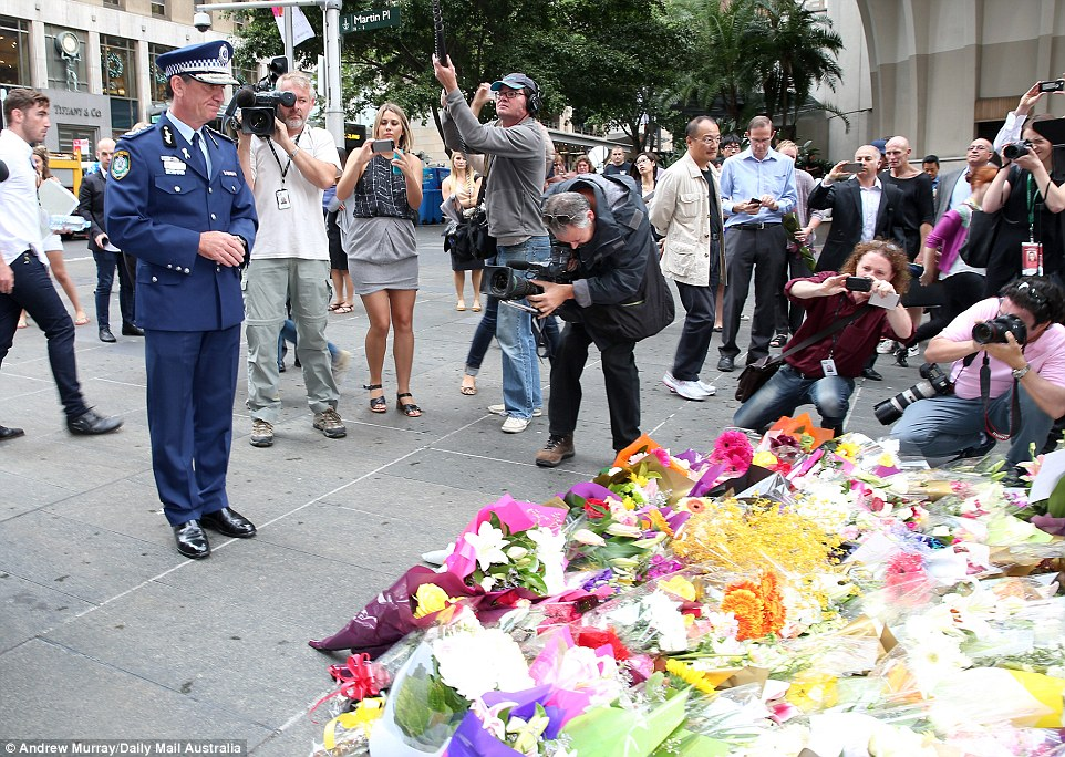 Observing the flowers: New South Wales Police Commissioner Andrew Scipione visited the scene outside the Lindt cafe on Tuesday morning