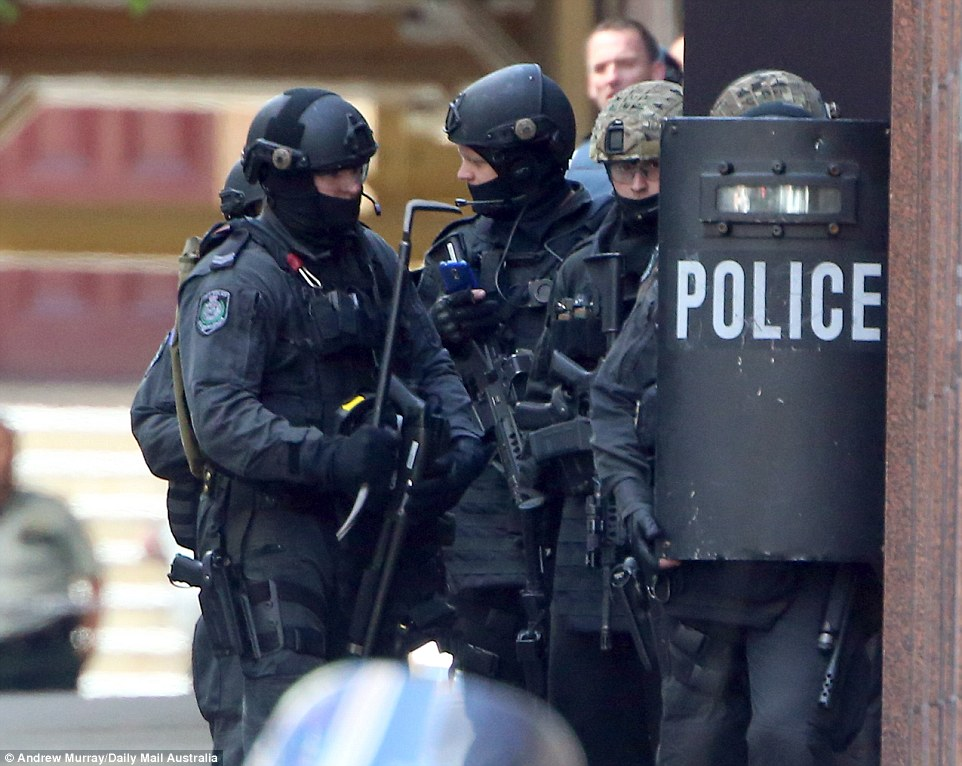Police are stationed behind a ballistic shield with weapons drawn outside the fire door where a hostage escaped from