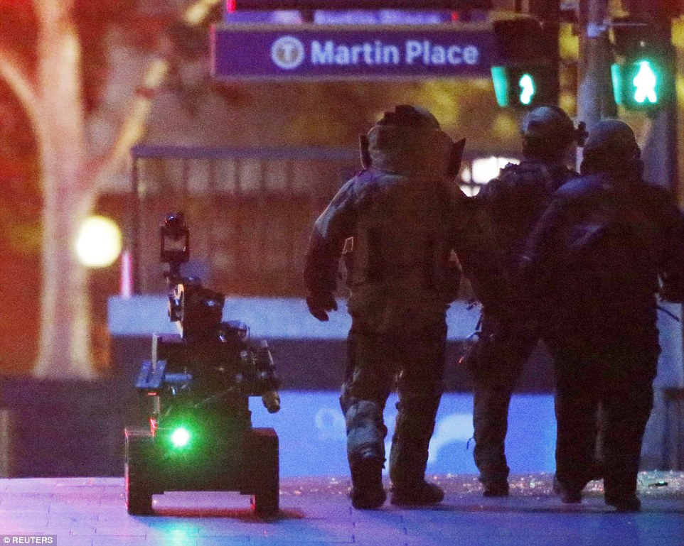 Police officers wearing armoured suits walk with a robot towards Lindt Cafe in Martin Place to check for booby traps after the siege ended