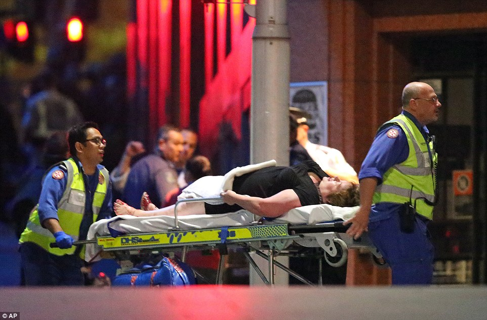 Response: An injured hostage is carried away on a stretcher by paramedics after police stormed the Lindt cafe in central Sydney