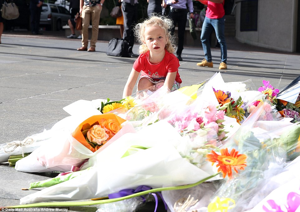 Four-year-old daughter Mona placed flowers with her family as hundreds of floral tributes started to appear in Martin Place