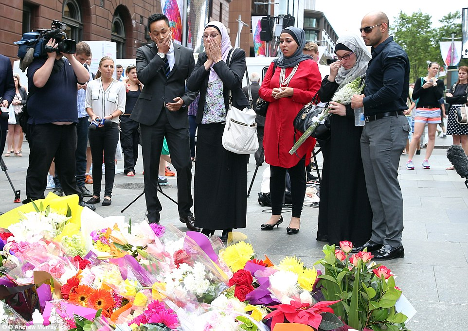 Visibily distraught men and women have been laying tributes for the two innocent victims of the siege