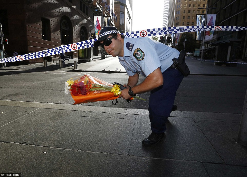 A NSW police officer carries floral tributes through an empty Martin Place early on Tuesday