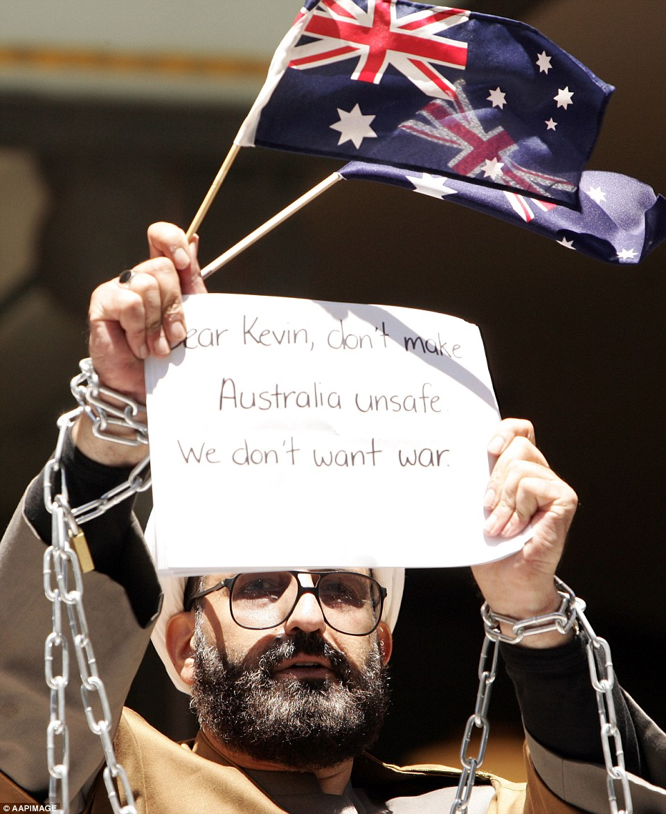 Chains: Gunman Man Haron Monis, pictured here protesting charges against him earlier this year, held 17 people hostage in the Lindt cafe