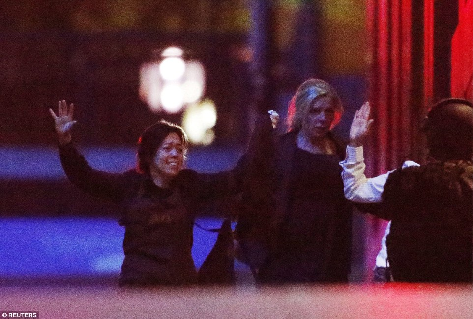 Shocking: With terror etched on their faces, two female hostages run into the arms of armed police at the back of the building
