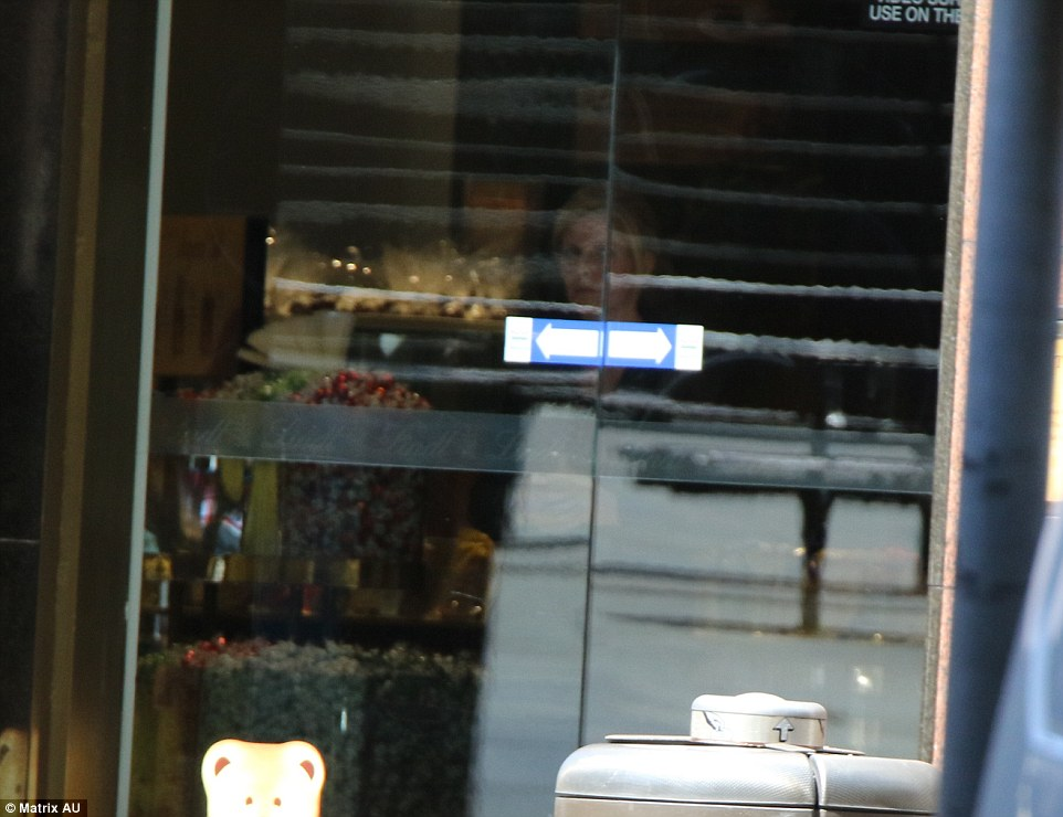 One blonde-haired hostage was pictured inside the cafethrough the glass doors standing in the middle of the shop