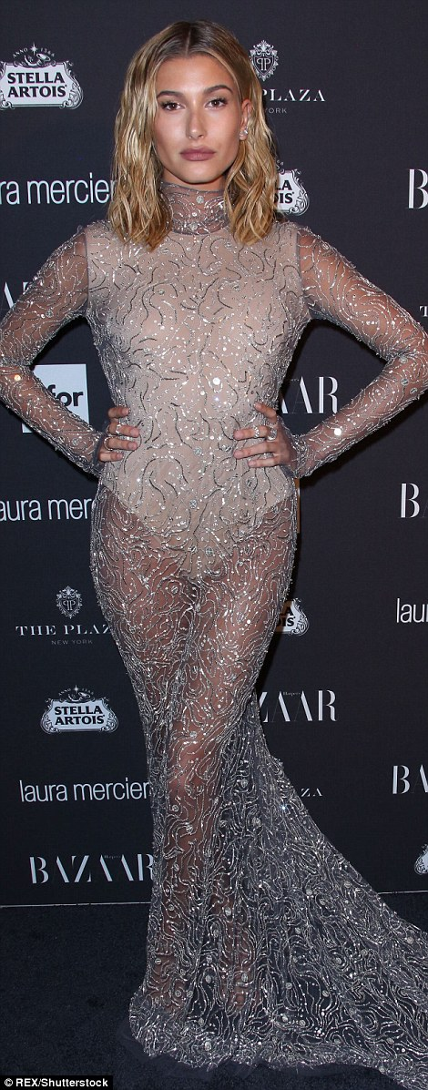 Absolutely dazzling: Hailey Baldwin glittered in a sheer gold dress featuring a cream bodysuit beneath