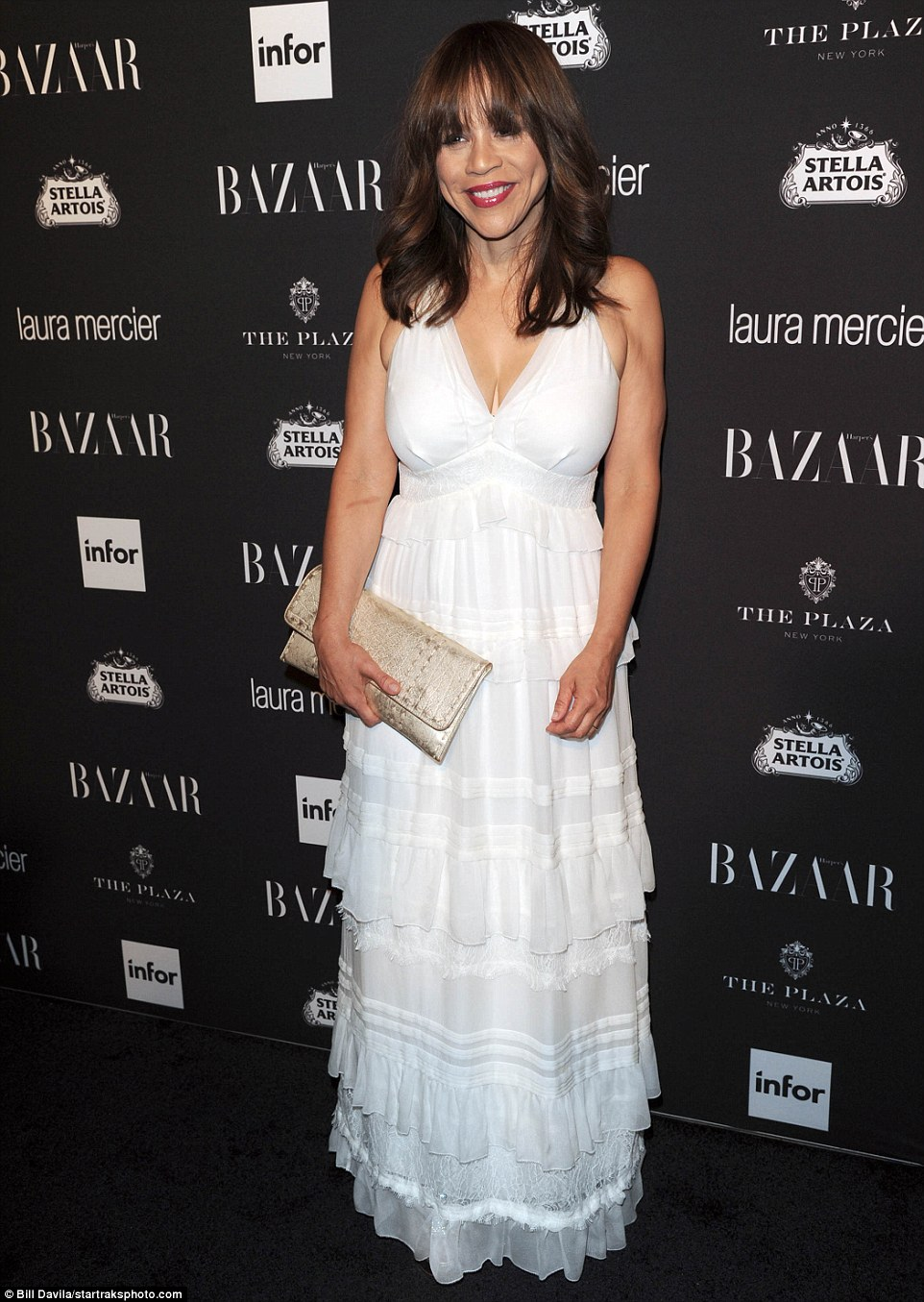 Such a pretty look: Rosie Perez wowed in a white layered frock, adding a gold clutch and shiny pink lipstick