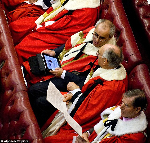 Online in Parliament: Peers study an iPad in the House of Lords during the state opening ceremony last year as figures laid bare what peers, MPs and their staff get up to on the internet