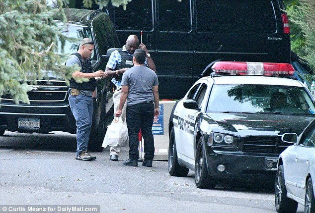 The guards talked to the man for about five minutes before the food was delivered. Clinton's black van can be seen in the background, perhaps suggesting she will be on the move soon