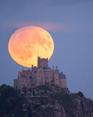 The harvest moon rises behind St Michael's Mount in Cornwall, UK. The harvest moon and eclipse will not occur at the same time again until 2024