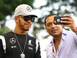Mercedes driver Lewis Hamilton of Britain poses for a selfie with a fan as he arrives at the Marina Bay City Circuit ahead of the Singapore Formula One Grand Prix in Singapore, Thursday, Sept. 15, 2016. (AP Photo/Yong Teck Lim)