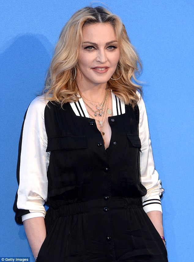 Teasing: Madonna buttoned down her dress to reveal a hint of cleavage