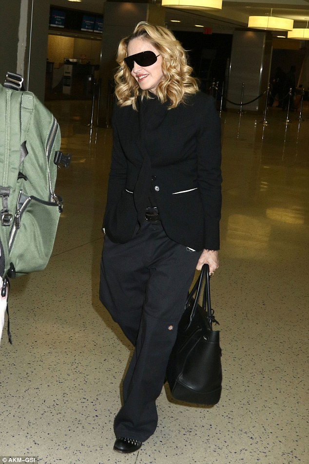 Undercover mother: She suffered an embarrassing nip slip the day before at a NYFW show; And on Sunday night Madonna made sure to cover up while catching a flight out of New York's JFK airport