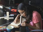 In this undated photo supplied by Ravi Naiknaware, Anushka Naiknaware works at her home in Beaverton, Ore, developing and testing a bandage that can tell medical workers when it's time for the dressing to be changed.  Naiknaware, 13,  finished in the top eight in an international science contest run by Google, won a $15,000 scholarship, a free trip to the Lego world headquarters in Denmark and a year's worth of entrepreneurship mentoring from a Lego executive. (Ravi Kaiknaware via AP)