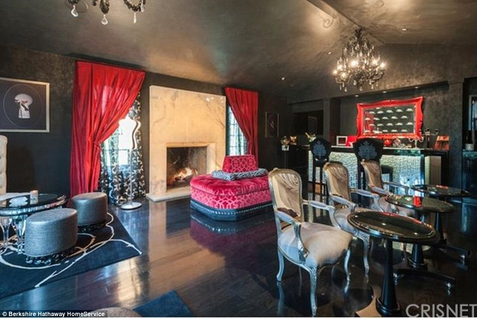 Hollywood glitz: The large lounge is more like a night club with a black and silver bar and matching bar stools, a red velvet banquette, red drapes and marble fireplace
