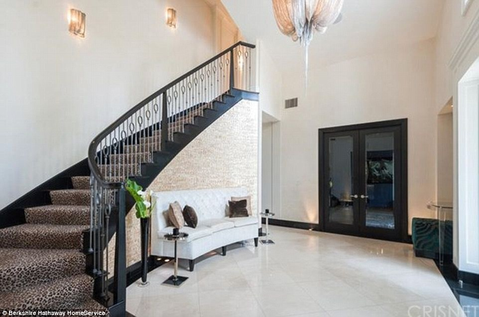 Welcome home; The formal entry has a marble floor and an impressive staircase with leopard-print carpeting