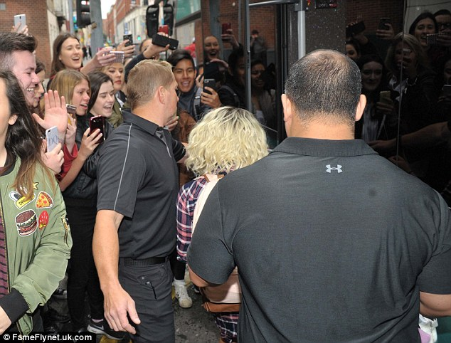 Pandemonium: She was ushered onto the bus as crowds of fans gathered to get a snap of her