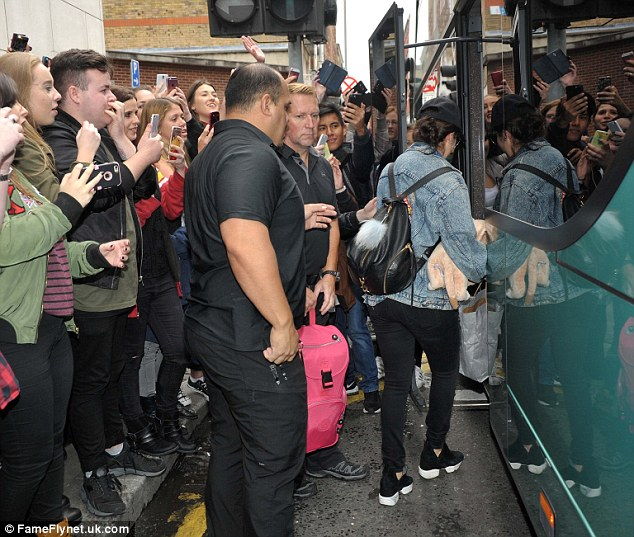 Heavy security: The bodyguards made sure fans stood well clear of the bandmates and the bus