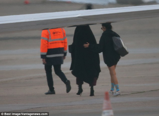 Kim Kardashian was rushed onto a plane bound for New York on Monday morning after being robbed at gunpoint (pictured, Kardashian and her personal assistant on the runway in Paris)