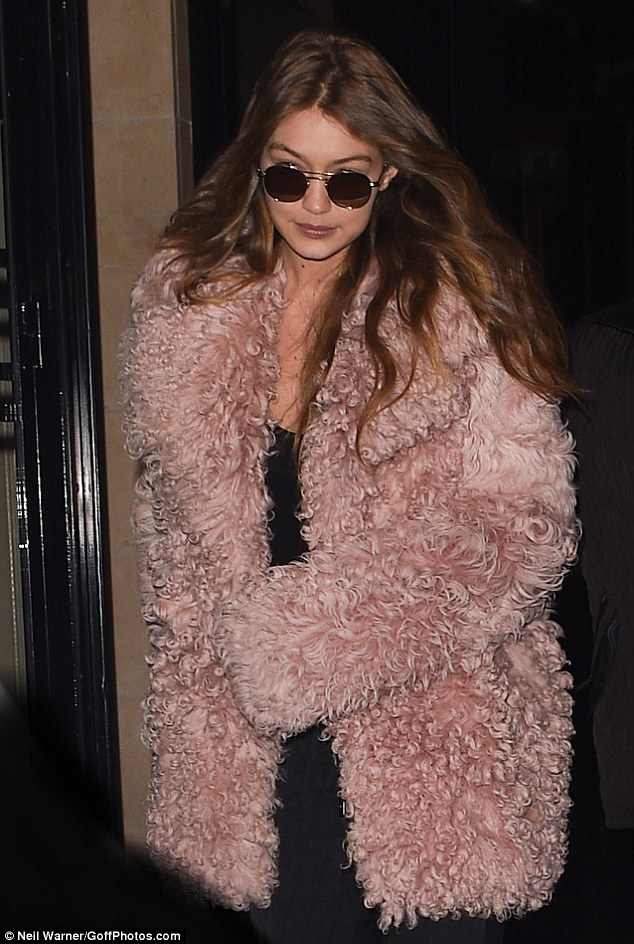 On the job:The American supermodel sported a fluffy pink coat over an otherwise understated ensemble while attending a late night fitting at high-end label Miu Miu's showroom in the French capital