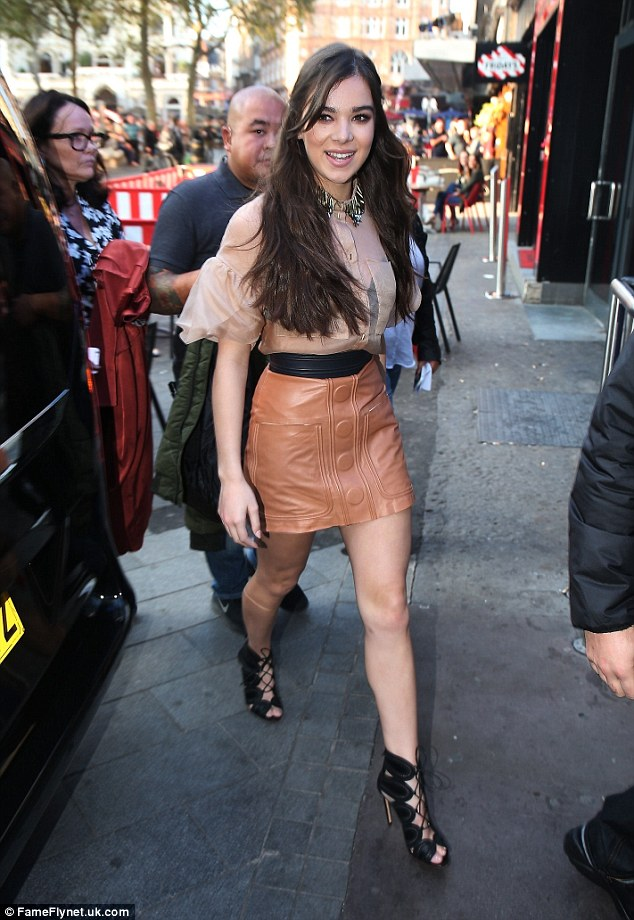 Stylish: The pretty youngster sizzled as she flashed her black bra in a sheer nude shirt