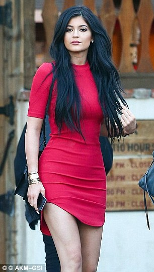 Lady in red: Another snap saw the brunette beauty wearing a skintight red dress with a curved daringly short hem - a then 17-year-old Kylie wore a very similar looking dress in Los Angeles last March (pictured)
