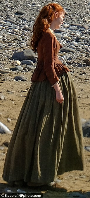 A bundle of joy on its way? Seen sporting a bulging belly on-location in Cornwall on Monday, Eleanor Tomlinson looked to be expecting an on-screen bundle of joy as she filmed a series of dramatic shots alongside co-star Aidan Turner