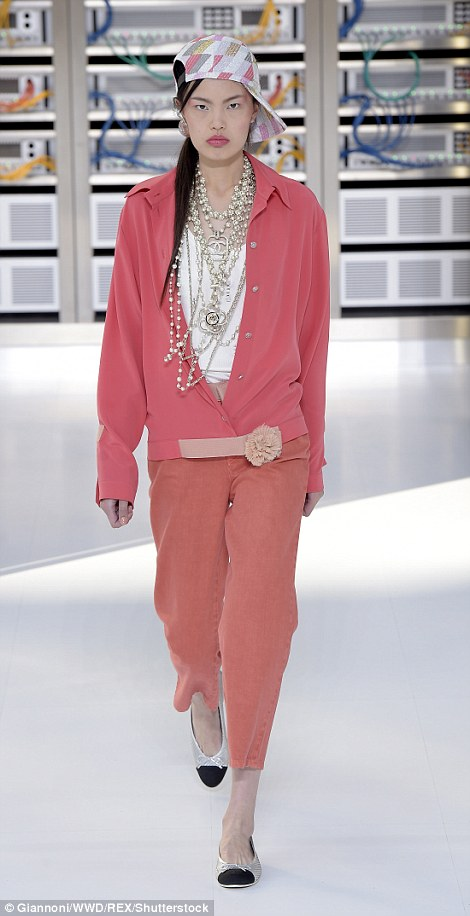 One model wore layers and layers of silver and pearl necklaces with oversized Chanel medallions on