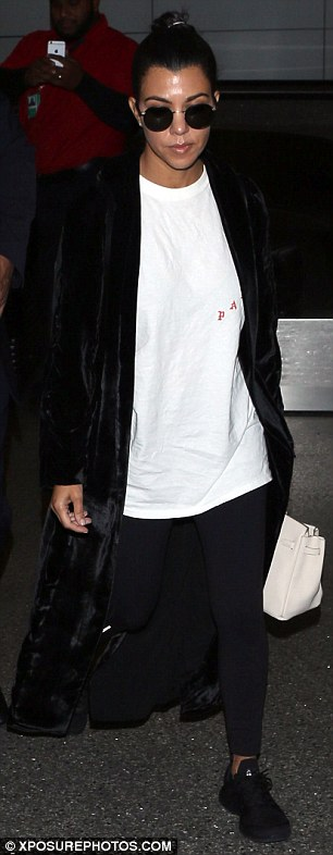 Low profile: Kourtney wore a baggy white T-shirt with a black coat, leggings and $140 APL 'TechLoom Pro' black trainers