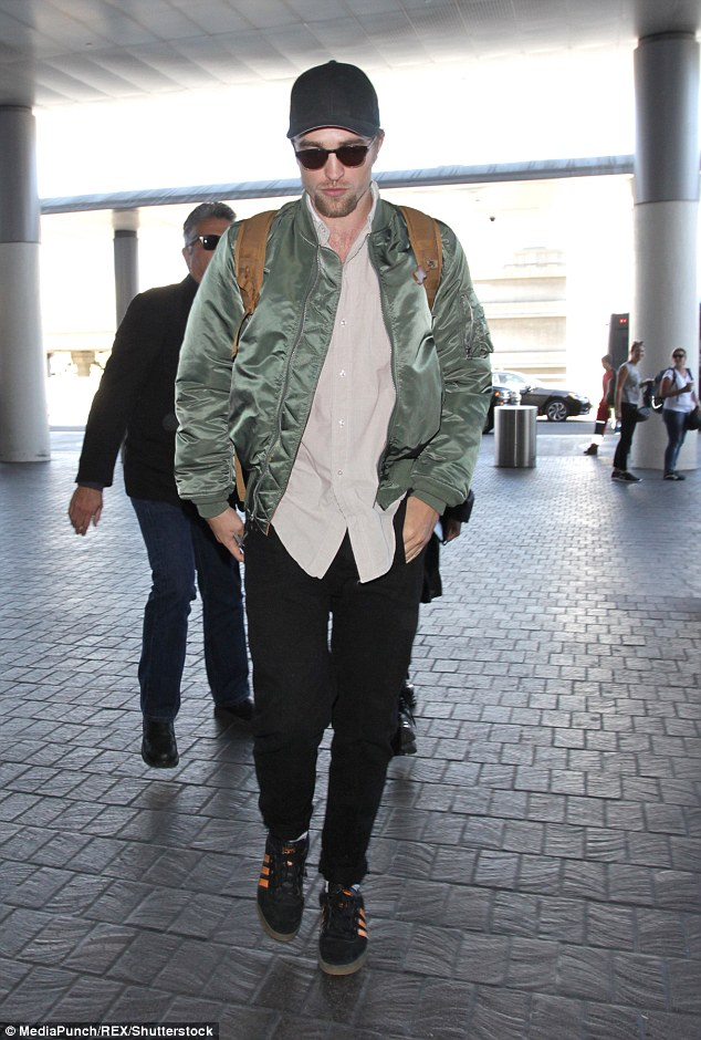 Style: The 30-year-old star arrived at the busy terminal wearing black jeans and orange and black Addidas trainers