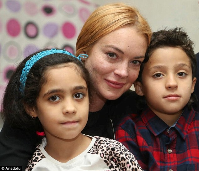 Big heart: Lohan seems comforted in this shot with Heya (left) and Leys, a pair of twins at the home she visited