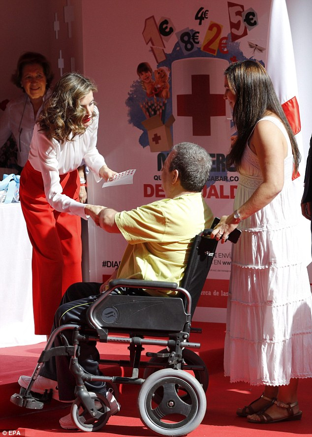 epa05571259 Spanish Queen Letizia (L) greets a man as he contributes with money during the 'Dia de la Banderita' (lit. Little Flag Day) at the Red Cross headquarters in Madrid, Spain, on 05 October 2016. During the little flag day volunteers all over the country take money boxes to the street to raise money for the Red Cross.  EPA/BALLESTEROS