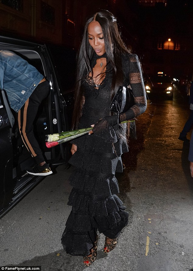 A rose for a rose: Naomi Campbell carried two flowers following a dinner date with 'old flame' Usher in Paris on Monday evening