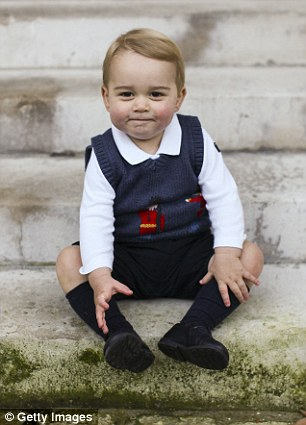 Prince George sits for his official Christmas picture in a courtyard at Kensington Palace in late November of 2014 wearing blue shorts