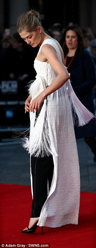 Fancy fringing: Rosamund was seen wrestling with the tassels hanging from her dramatic dress on the red carpet