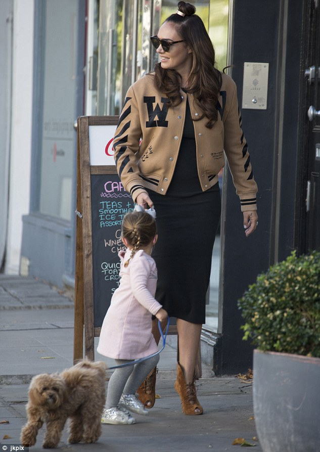 Stylish pair: Heading out into Notting Hill for a walk with the family pooch, the 32-year-old Formula One heiress cut a chic figure in a camel varsity jacket
