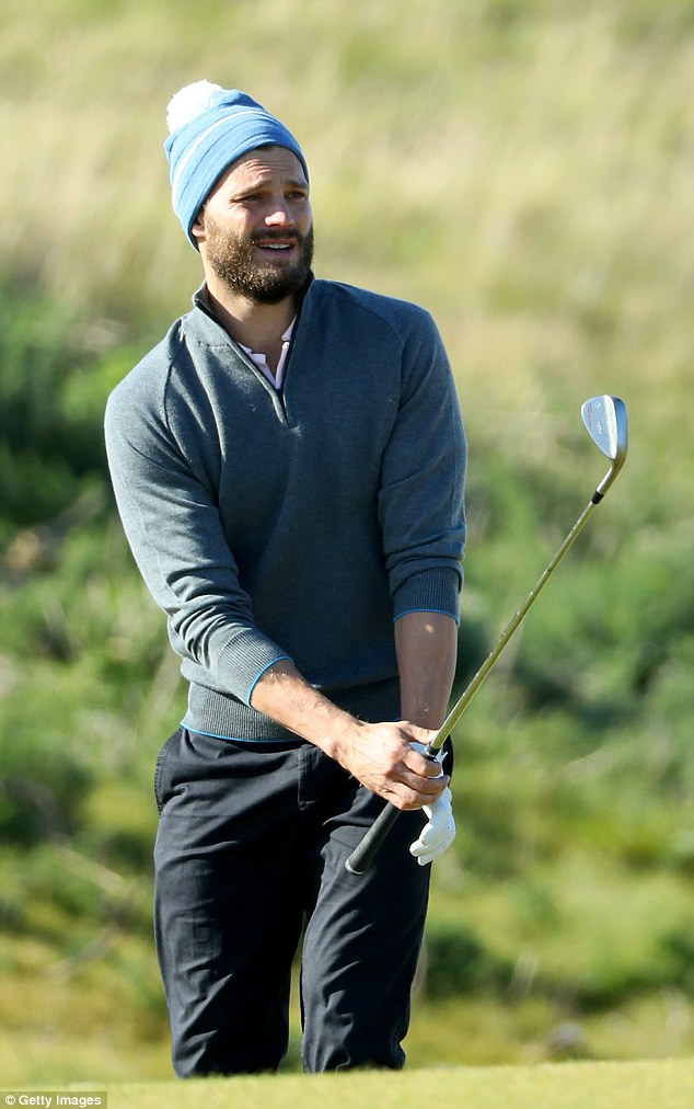 Keeping cosy: Jamie wore a beanie hat to keep the chill out on the course