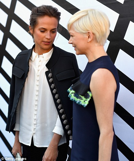 Flirty look:The 36-year-old Blue Valentine actress ensured she stood out among the stars as she slipped into a flirty navy shift dress with a dainty mint green frill along the bust (pictured with AliciaVikander)