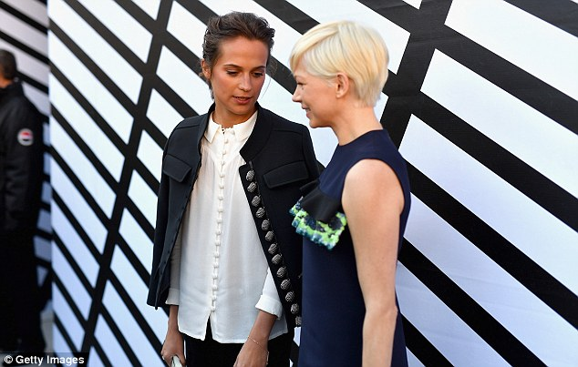 Flirty look: The 36-year-old Blue Valentine actress ensured she stood out among the stars as she slipped into a flirty navy shift dress with a dainty mint green frill along the bust (pictured with Alicia Vikander)