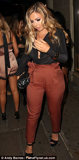 Flattering: The gym-bunny accentuated her figure in the high-waisted rust trousers which cinched in at her waist before hugging her shapely legs to the ankle