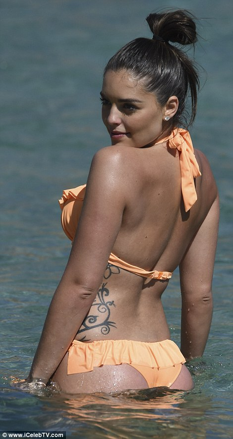 Perky posterior:The 23-year-old Australian beauty, the half-sister of singer and actress Holly Candy, looked absolutely phenomenal in a frilled orange bikini which made the most of her ample bosom and incredible abs