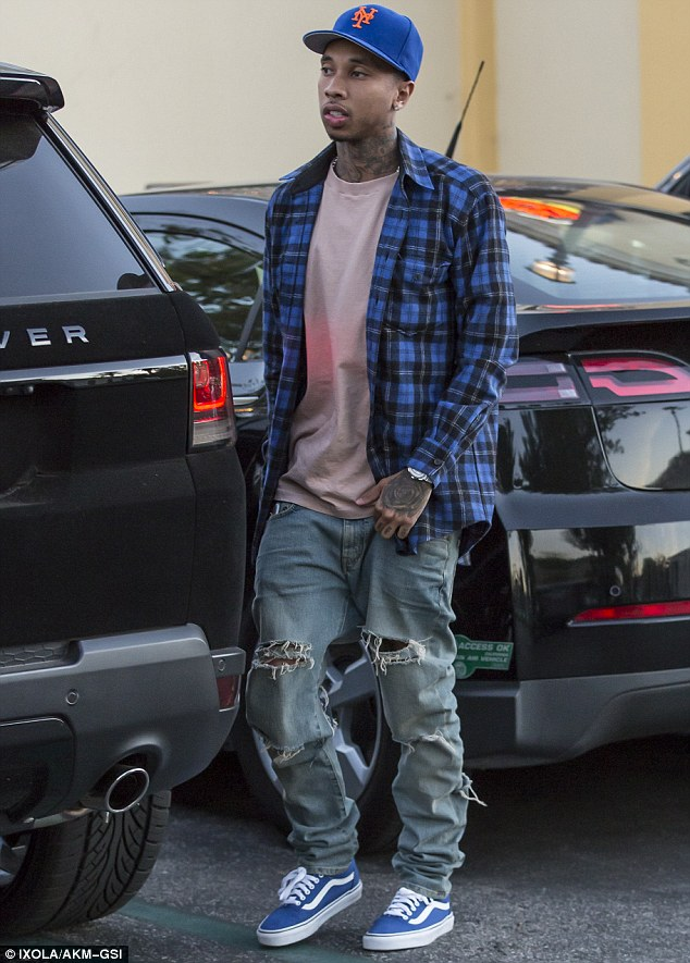 Keeping it casual: Tyga was clad in ripped jeans, a plaid shirt and a blue baseball cap