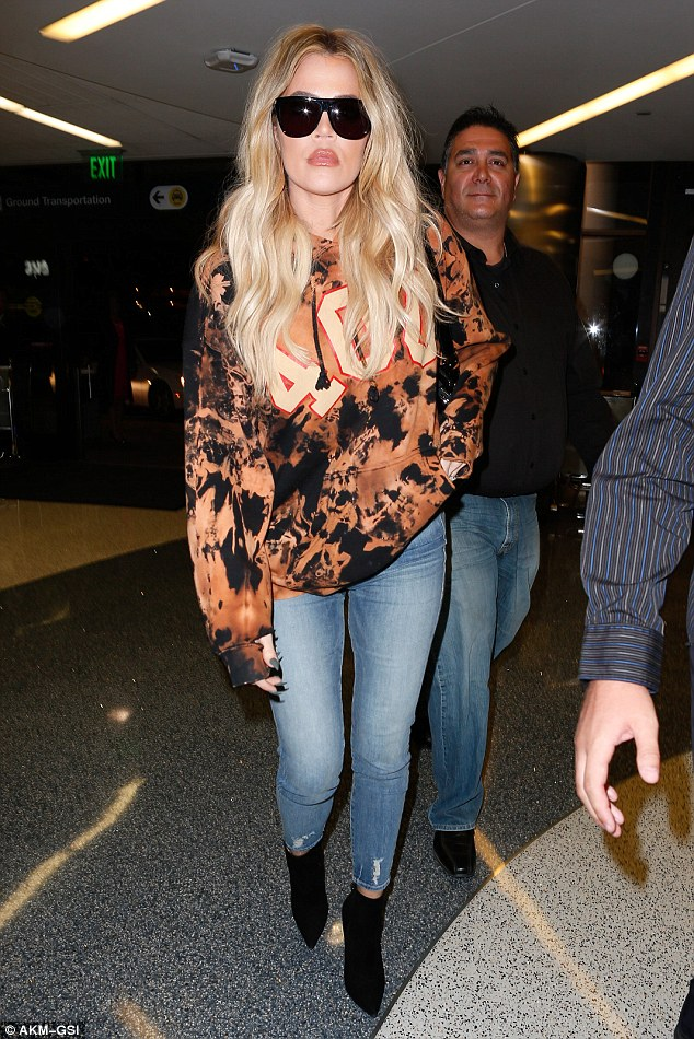 Taking no chances: Khloé Kardashian put on a serious appearance as she arrived at LAX flanked by three security guards