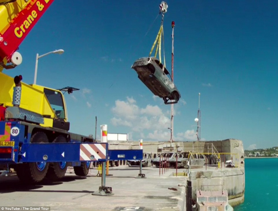 During the dramatic 94-second clip, the trio try and manoeuvre a car by using a huge crane next to the sea