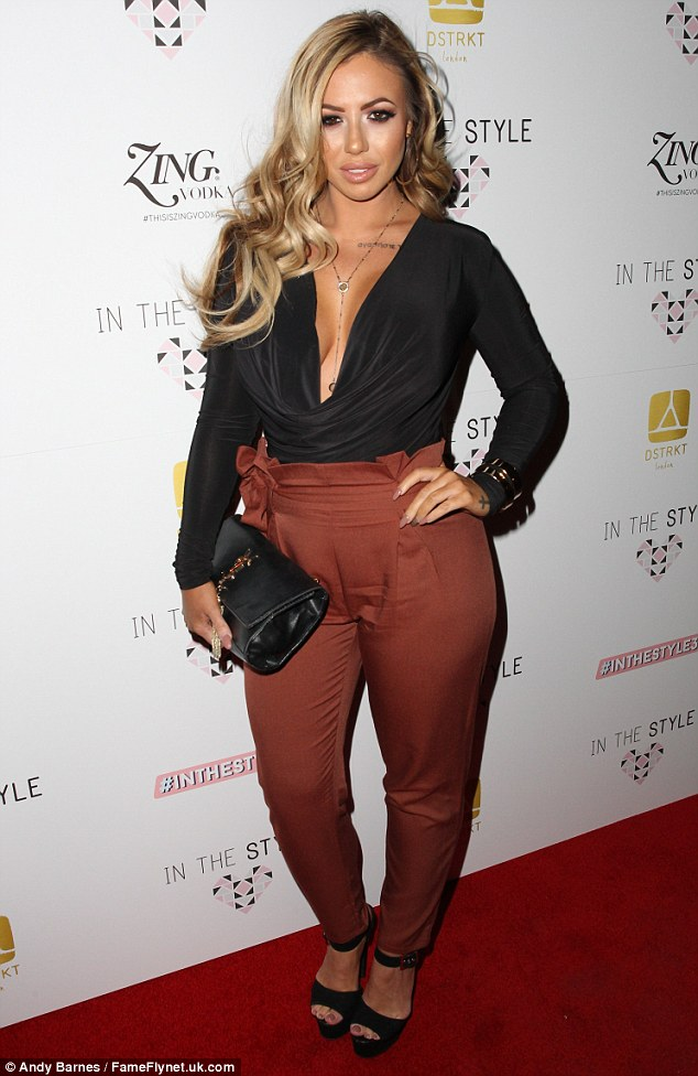 Star of the show:Holly paired the strides with a black ruched top which featured a daring V neckline, extending far past her chest to showcase her famously rounded assets