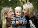 In this photo taken Tuesday, Sept. 20, 2016, Albin's mother Emelie Eriksson, left, smiles as she poses for a photo with her son and her mother Marie, right, outside her home in Bergshamra, Sweden. Eriksson was the first woman to have a baby after receiving a womb transplant from her mother, a revolutionary operation that links three generations of their family. (AP Photo/ Niklas Larsson)