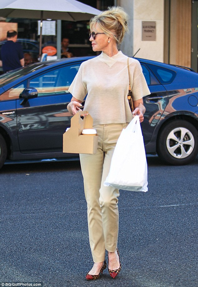 Coffee run: Melanie kept her accessories simple as she enjoyed her quick outing, wearing oversized gold-rimmed sunglasses and a small Louis Vuitton clutch bag