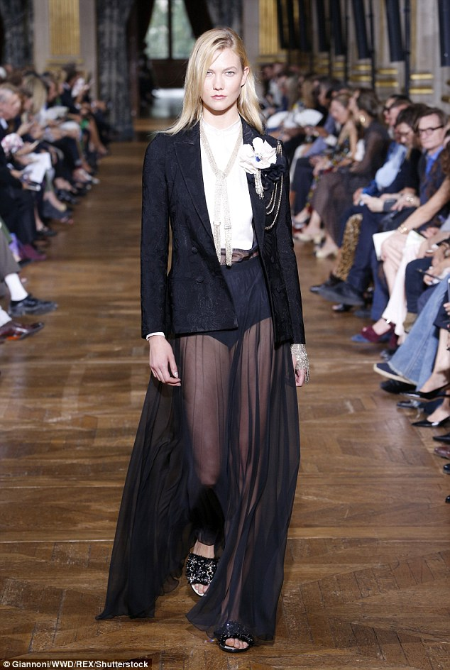 Runway star: After arriving Karlie made a quick change for the runway where her look combined a business blazer with a billowing sheer skirt with wide-set pleats